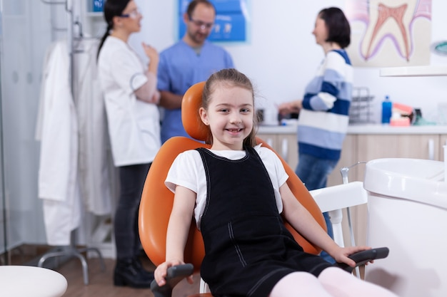 Маленькая девочка в кабинете дендистрии показывает молочный зуб, пока родители обсуждают с врачом-дантистом. ребенок с матерью во время осмотра зубов у стоматолога, сидящего на стуле.