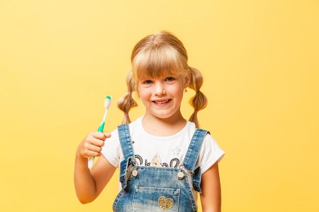 Маленькая девочка в джинсовых комбинезонах чистит зубы зубной щеткой. концепция ежедневной гигиены.