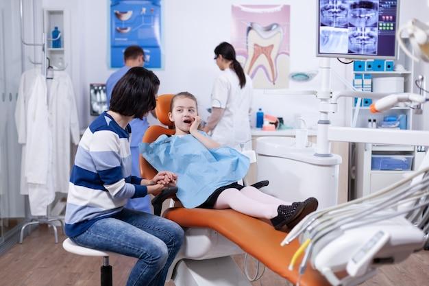 手と痛みを伴う表情で口に触れる歯科医院の少女。歯の間に母親と一緒にいる子供は、椅子に座っている口内検査で診察します。