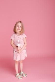 드레스와 분홍색 표면에 우유의 유리에 어린 소녀