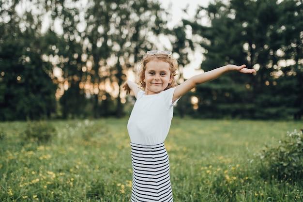 Маленькая девочка в платье показывает на открытом воздухе