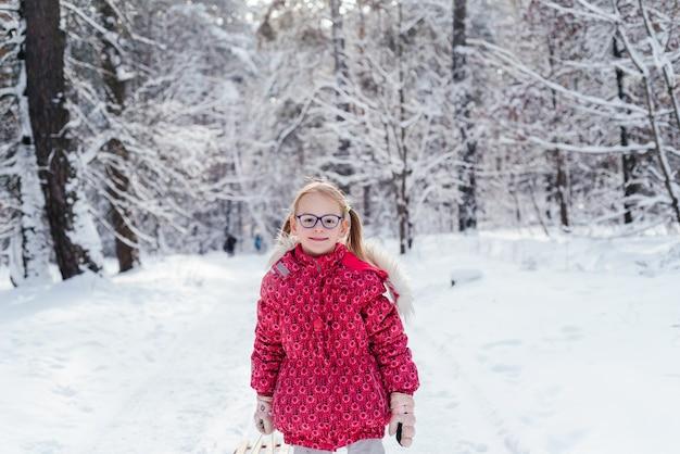 Маленькая девочка в очках тянет сани через красивый зимний лес
