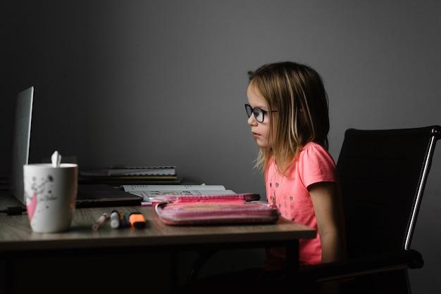 Маленькая девочка в очках учится онлайн и использует свой ноутбук дома