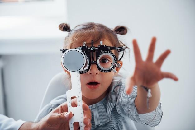 안과 클리닉에서 안경을 쓴 어린 소녀는 시력 검사를 받았습니다.