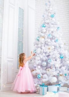 Маленькая девочка в маскарадном костюме украшает огромную белую елку