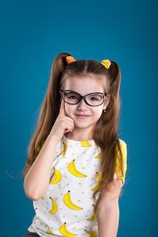 青の背景にメガネとバナナのtシャツの少女