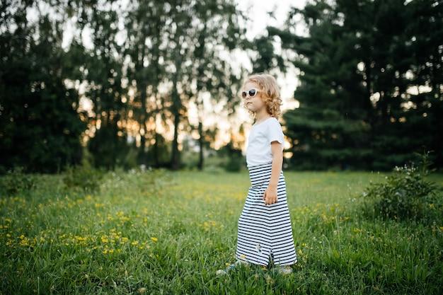 Маленькая девочка в очках и платьях позирует на открытом воздухе