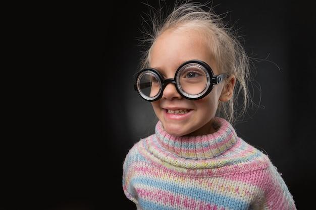 眼鏡をかけた少女が顔を作る