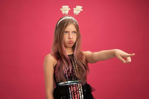 キラキラパーティードレスとピンクの背景の上に立っている何か新年のお祝いの休日の概念を人差し指で指している深刻な顔で脇を見て面白いヘッドバンドの少女