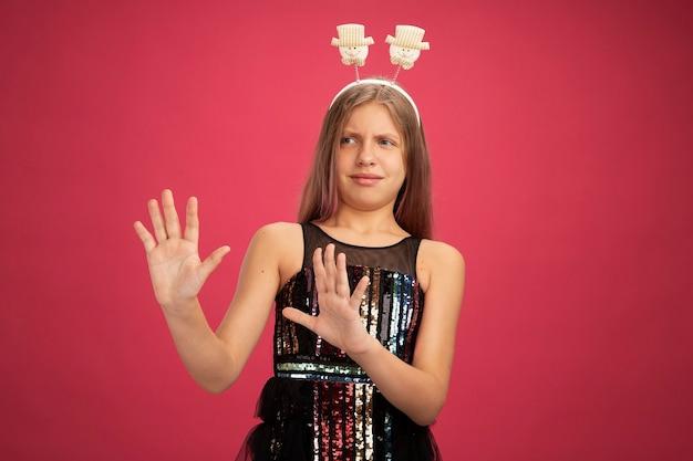 キラキラパーティードレスとピンクの背景の上に立っている新年のお祝いの休日のコンセプトを手を差し伸べて心配して脇を見て面白いヘッドバンドの少女