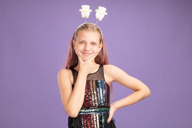 반짝이 파티 드레스와 보라색 배경 위에 유쾌하게 서있는 행복한 얼굴로 카메라를보고 재미있는 머리띠에 어린 소녀