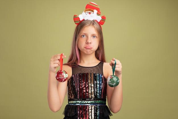 Маленькая девочка в блестящем праздничном платье и повязке на голову с санта, держащим елочные шары, глядя в камеру, смущенная и недовольная, стоя на зеленом фоне