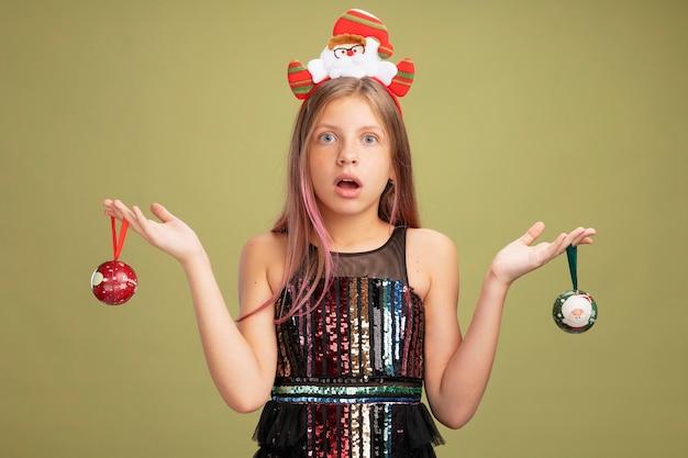 Маленькая девочка в блестящем праздничном платье и повязке на голову с санта, держащим елочные шары, глядя в камеру, смущенная и удивленная, стоя на зеленом фоне