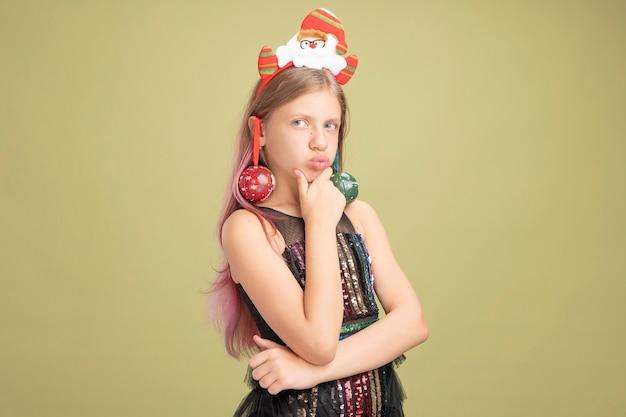 キラキラのパーティードレスと彼女の耳にクリスマスボールを持ったサンタのヘッドバンドの少女は、緑の壁の上に立っている真面目な顔で考えているあごに手を置いて脇を見ています