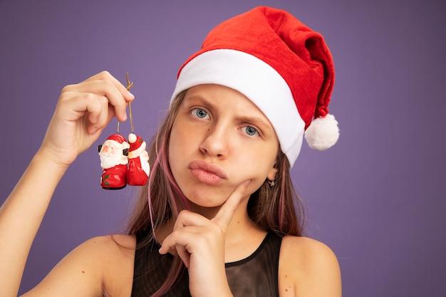 キラキラパーティードレスとサンタの帽子をかぶった少女が紫色の背景の上に立っている深刻な顔でカメラを見てクリスマスのおもちゃを保持しています