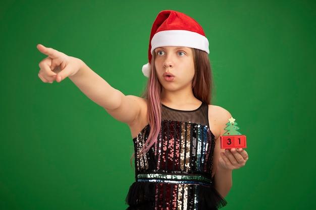 キラキラパーティードレスとサンタの帽子をかぶった少女は、緑の背景の上に立っている側に人差し指で指して驚いたものを見て、新年の日付でおもちゃの立方体を保持しています