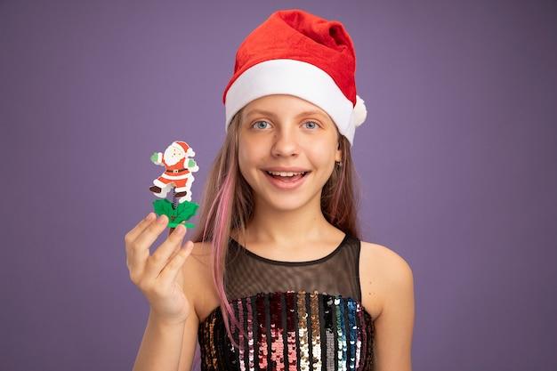 キラキラパーティードレスとサンタの帽子の少女は、紫色の背景の上に立っている顔に笑顔でカメラを見てクリスマスのおもちゃを示しています