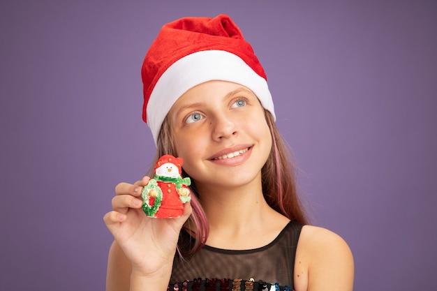 Маленькая девочка в блестящем платье и шляпе санта-клауса показывает рождественскую игрушку, глядя вверх с улыбкой на лице, стоя на фиолетовом фоне