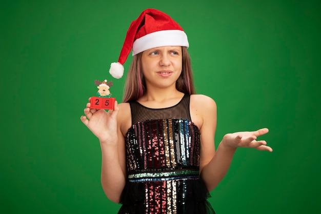 キラキラのパーティードレスとサンタの帽子をかぶった少女が、緑の背景の上に立って不満を持って手を上げて混乱し、不機嫌になって、日付25のおもちゃの立方体を示しています