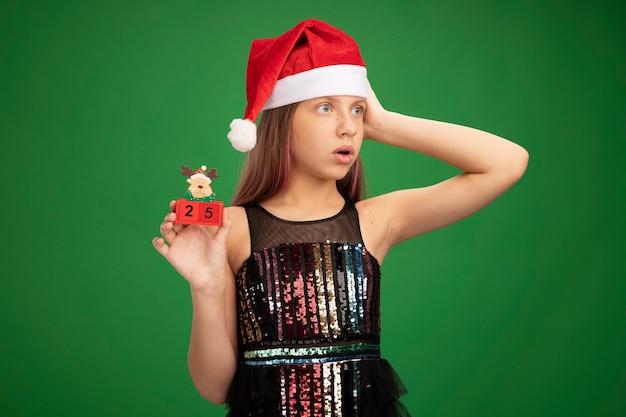 キラキラのパーティードレスとサンタの帽子をかぶった少女が、緑の背景の上に立って驚いて脇を見て、日付25のおもちゃの立方体を示しています