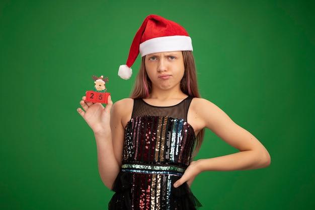 キラキラパーティードレスとサンタの帽子をかぶった少女は、緑の背景の上に立って不機嫌なカメラを見て日付25のおもちゃの立方体を示しています