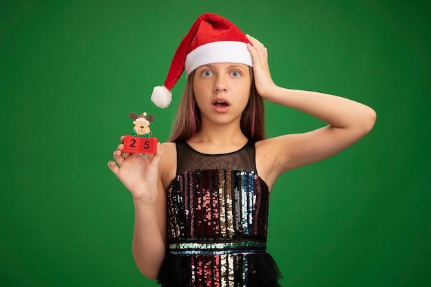 キラキラのパーティードレスとサンタの帽子をかぶった少女が、緑の背景の上に立っている彼女の頭に手を当てて驚いて驚いたカメラを見て、日付25のおもちゃの立方体を示しています
