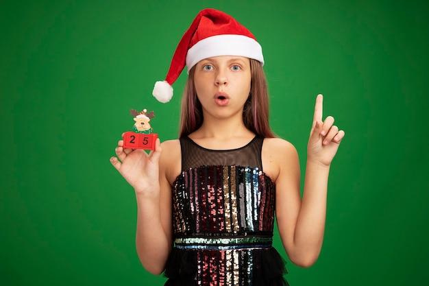 キラキラパーティードレスとサンタの帽子をかぶった少女は、緑の背景の上に立っている人差し指を示して驚いて見える日付25のおもちゃの立方体を示しています