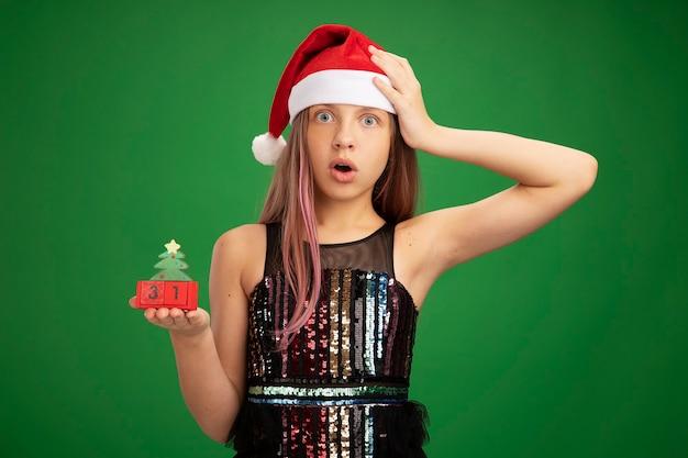 キラキラパーティードレスとサンタの帽子をかぶった少女は、緑の背景の上に立っている彼女の頭に手で驚いて驚いたカメラを見て新年の日付でおもちゃの立方体を示しています