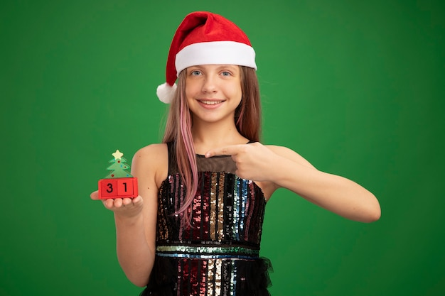キラキラパーティードレスとサンタの帽子をかぶった少女は、緑の背景の上に元気に立って笑って人差し指で指している新年の日付とおもちゃの立方体を示しています