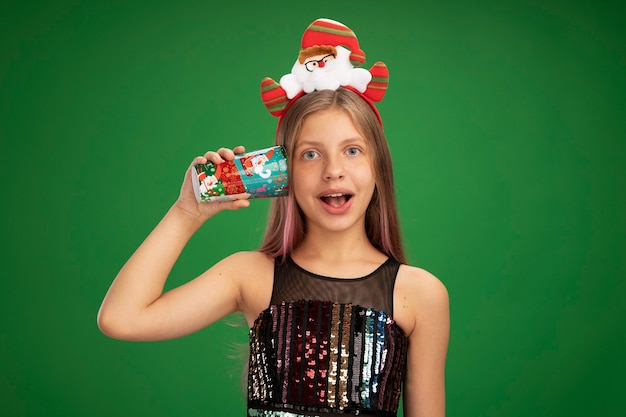 キラキラパーティードレスとサンタのヘッドバンドの少女は、緑の背景の上に元気に立って微笑んで彼女の耳にカラフルな紙コップを保持しています