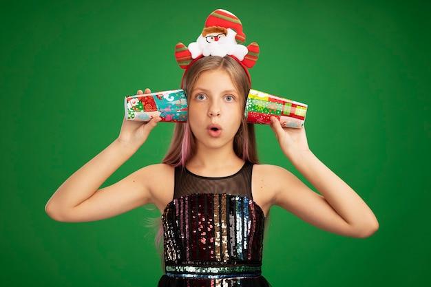 キラキラパーティードレスとサンタのヘッドバンドの少女は、緑の背景の上に立って驚いて見える彼女の耳の上にカラフルな紙コップを保持しています