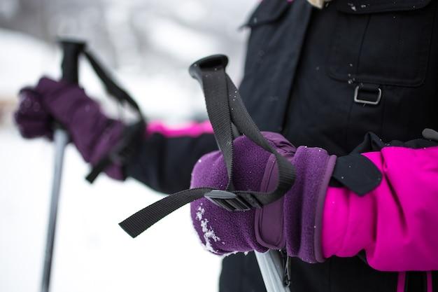 Маленькая девочка в перчатках с лыжными палками