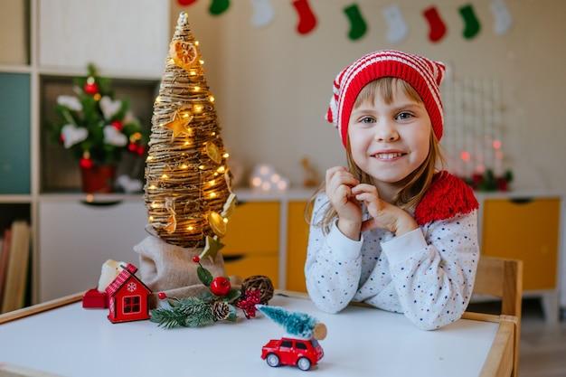 Маленькая девочка в шляпе гнома в детской комнате