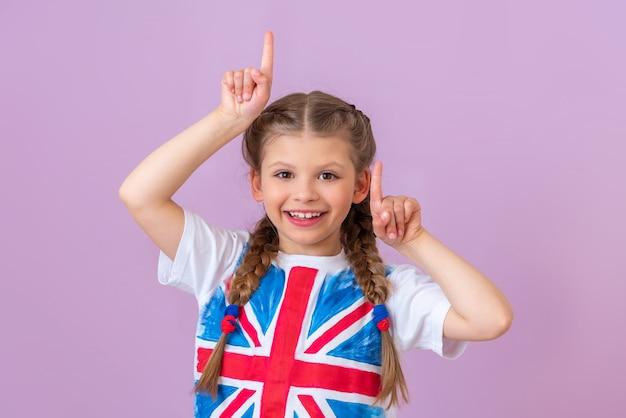 Маленькая девочка в футболке с флагом великобритании показывает вверх на светло-фиолетовом фоне