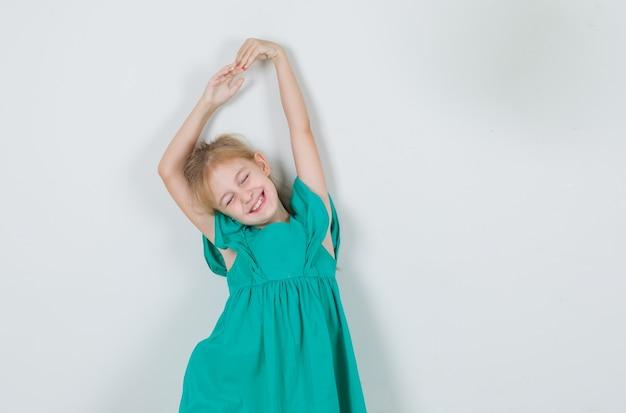 Маленькая девочка в зеленом платье протягивает руки с закрытыми глазами и выглядит весело