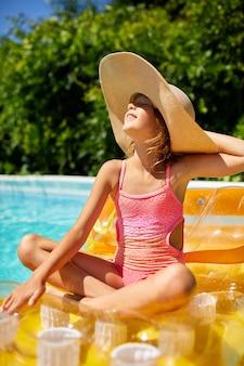 수영장에서 편안한 모자에있는 어린 소녀는 풍선 노란색 매트리스에서 수영하고 가족 휴가, 열대 휴양지에서 물 속에서 재미를 느낍니다.