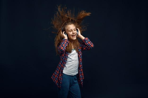 Маленькая девочка в наушниках против мощного воздушного потока в студии