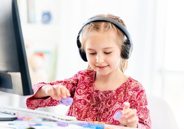 Маленькая девочка в наушниках делает школьную задачу с числами перед компьютером