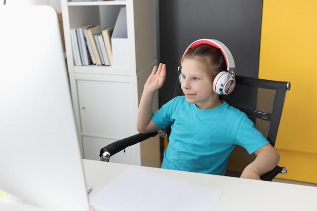 컴퓨터 앞에서 헤드폰에 어린 소녀는 인사말에서 수업을 제기