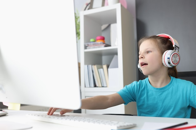 ヘッドフォンの少女はリモートでトレーニングに従事しています