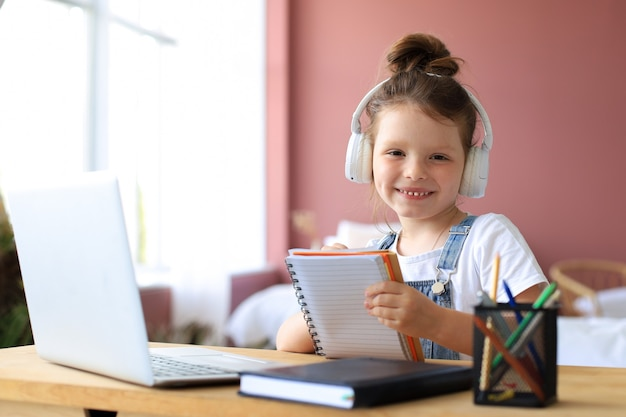 Маленькая девочка в наушниках сидит за столом, пишет в тетради, изучает онлайн, делает упражнения дома, маленький ребенок пишет от руки, готовит домашнее задание на карантине, имеет веб-класс или урок в помещении.