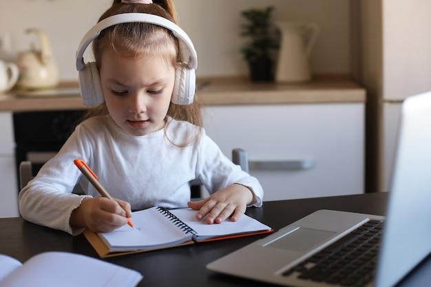 헤드폰을 끼고 책상에 앉아 온라인으로 공부하는 노트북으로 글을 쓰고 있는 어린 소녀는 집에서 연습을 하고, 어린 아이는 손글씨로 집에서 숙제를 준비하고, 웹 수업이나 실내 수업을 합니다.