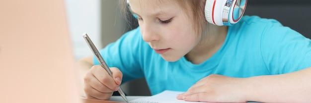 헤드폰을 끼고 노트북 앞에 테이블에 앉아 그림을 그리는 어린 소녀