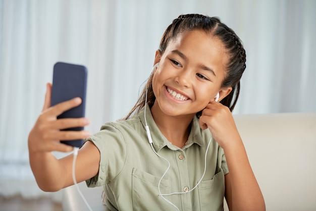 彼女の携帯電話で自分撮りをしながらカメラに微笑んでいるヘッドフォンの少女