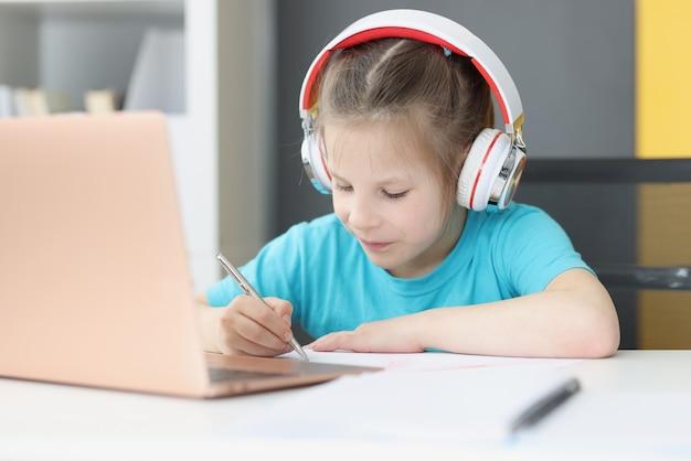 自宅のラップトップの前で自宅で勉強しているヘッドフォンの少女