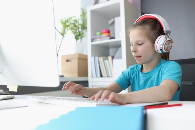 집에서 컴퓨터 키보드에 입력하는 헤드폰에 어린 소녀