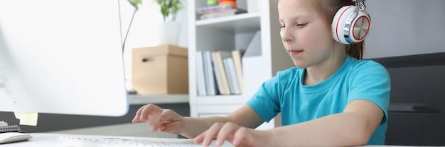 Маленькая девочка в наушниках, набрав на клавиатуре компьютера дома