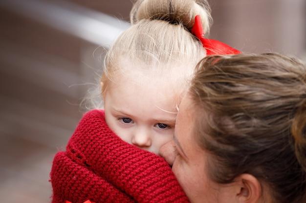 彼女の母親の腕の中で小さな女の子。閉じる