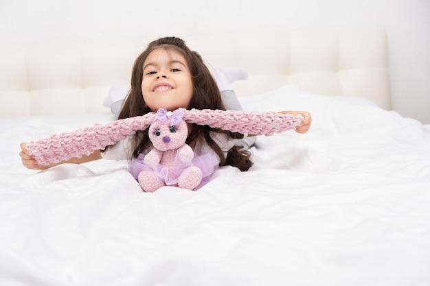 Маленькая девочка в домашней одежде сидит с плюшевым кроликом на кровати у себя дома.