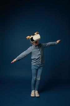 Маленькая девочка в джинсах и рубашке с очками гарнитуры виртуальной реальности изолированы